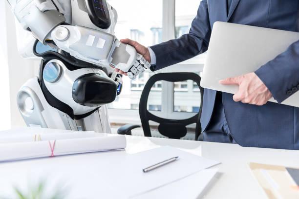 homem com laptop é apertando as mãos com o android - robô - fotografias e filmes do acervo