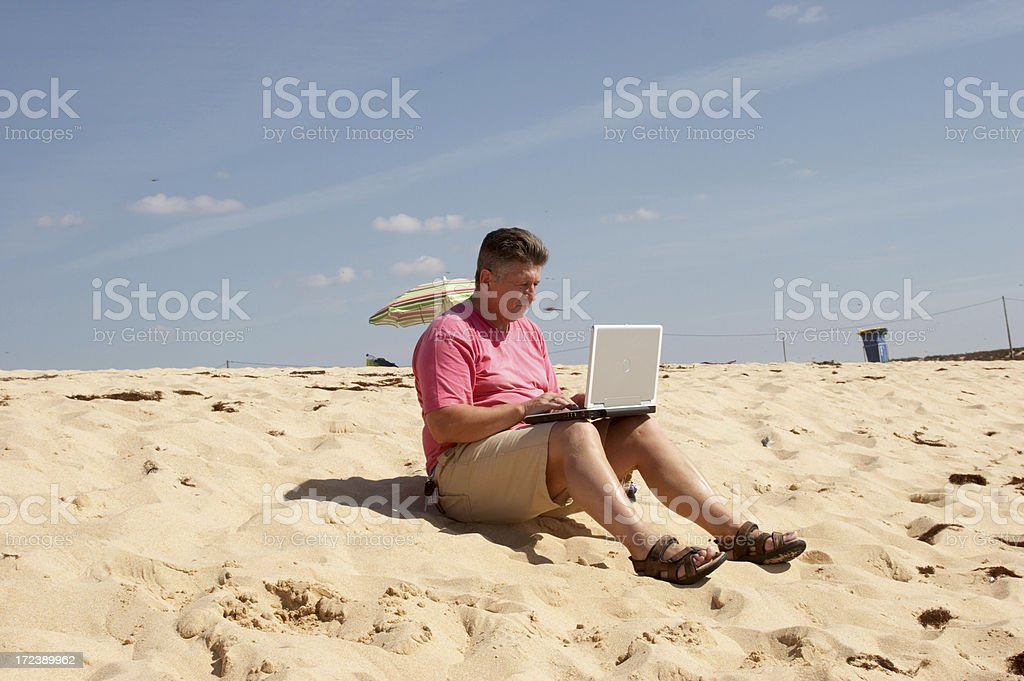 Man with laptop on beach royalty-free stock photo