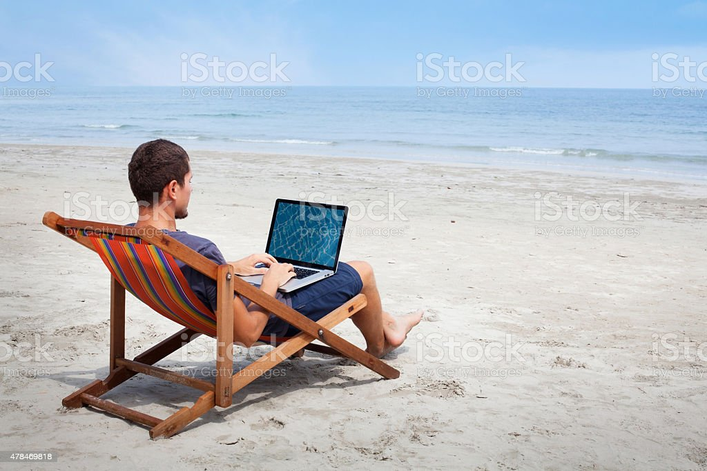 man with laptop on the beach stock photo