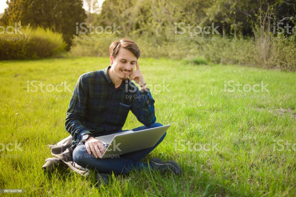 Man with laptop on the lawn stock photo