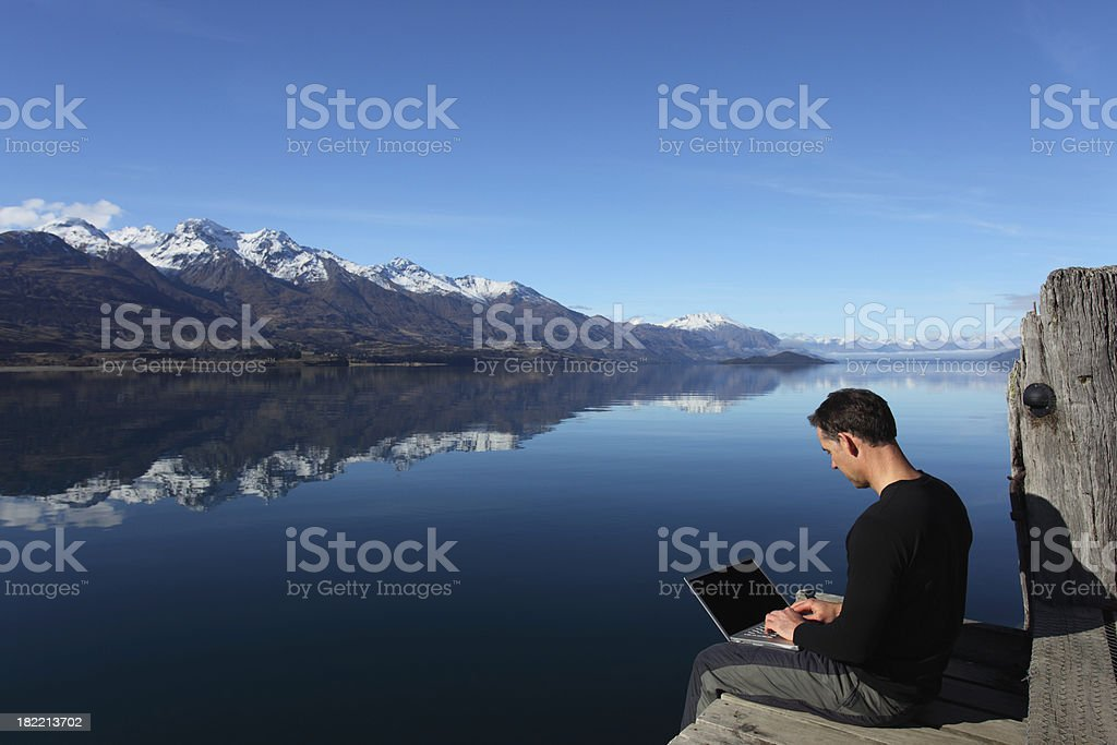 Man with laptop outdoors stock photo
