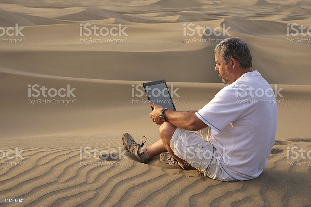 Man with laptop sitting in the desert. stock photo