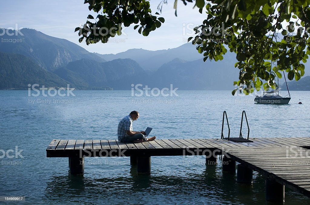 Man with laptop sitting on a jetty royalty-free stock photo