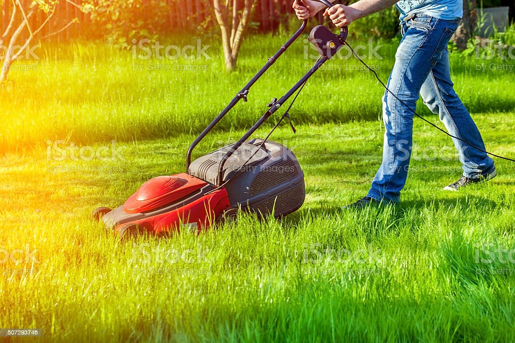 Man with lawnmower stock photo