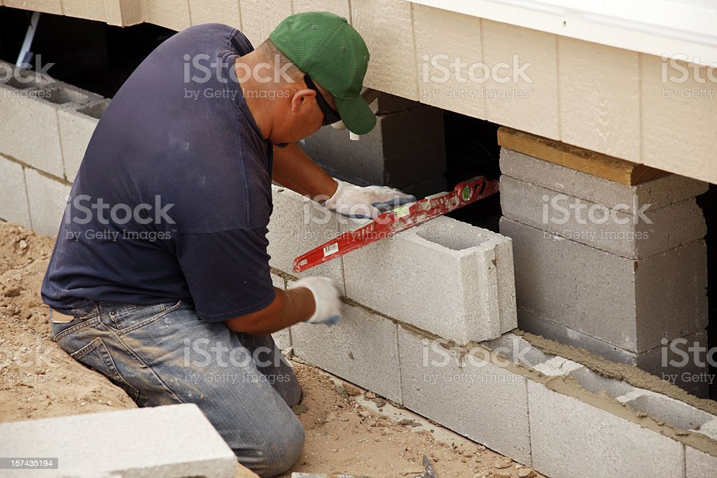 Man with Level Laying Concrete Block Skirting stock photo