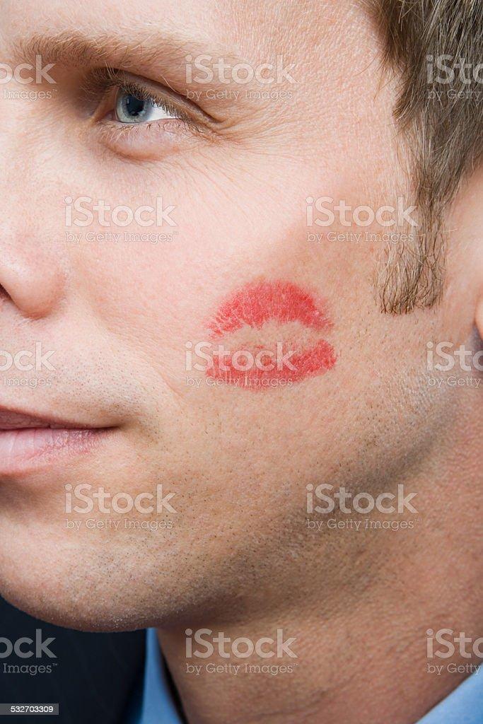 Man with lipstick kiss on cheek stock photo