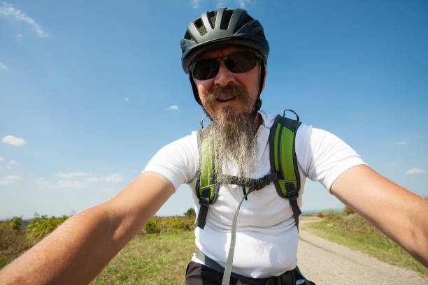 Man with long beard riding mountain bicycle outdoors stock photo
