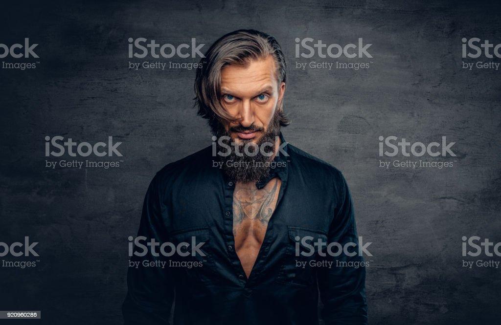 Un Homme Avec Les Cheveux Longs Et Tatouages Sur Sa Poitrine Habille