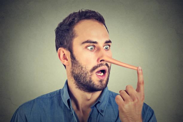 mann mit langer nase auf graue wand hintergrund isoliert. lügner-konzept - wahre lügen stock-fotos und bilder