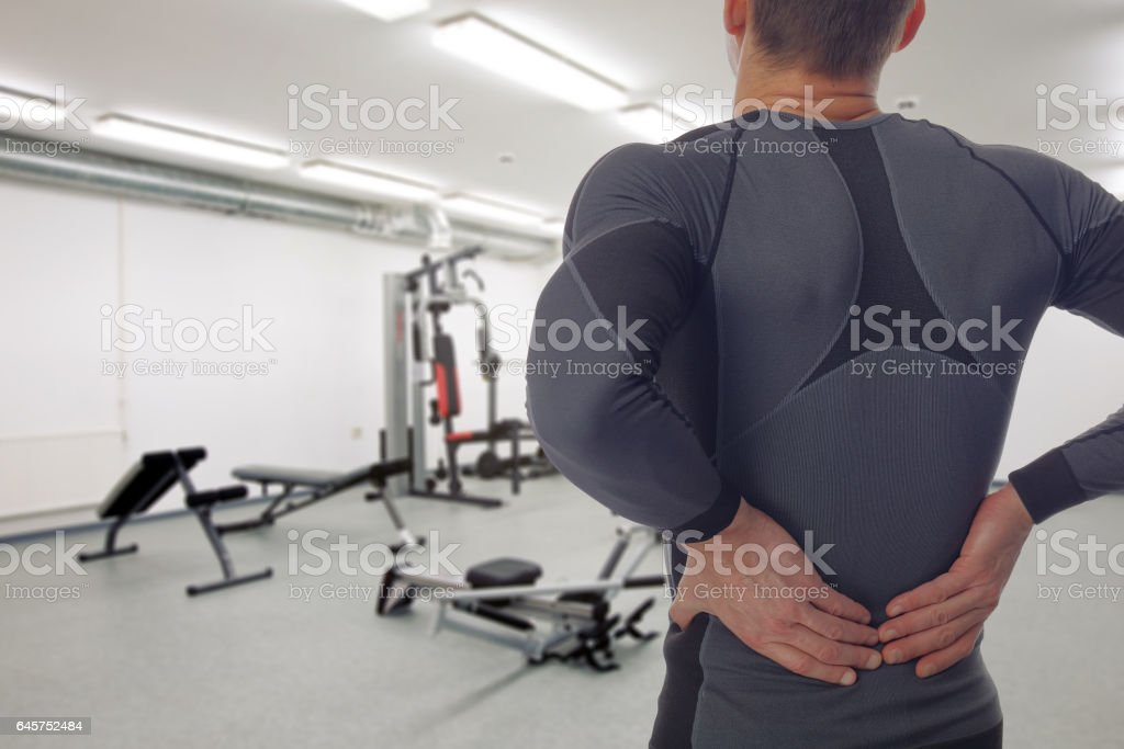 Man with low back pain in gym. Sports exercising injury stock photo