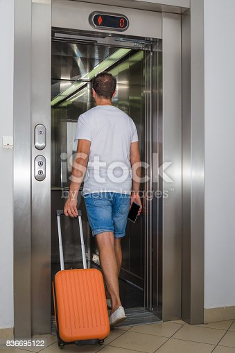 638591126istockphoto Man with luggage entering the elevator 836695122