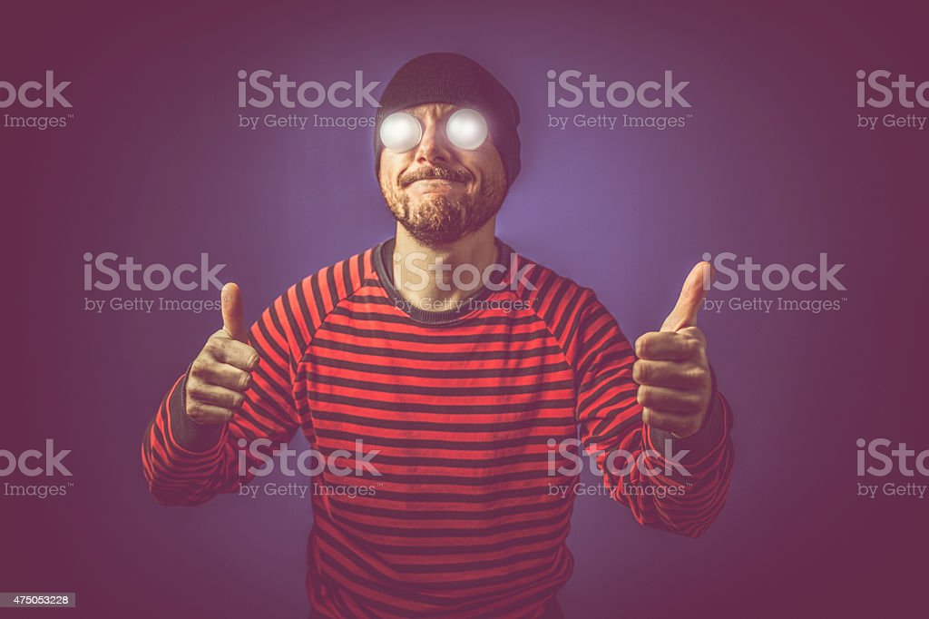 Man with luminous eyes thumbs up stock photo