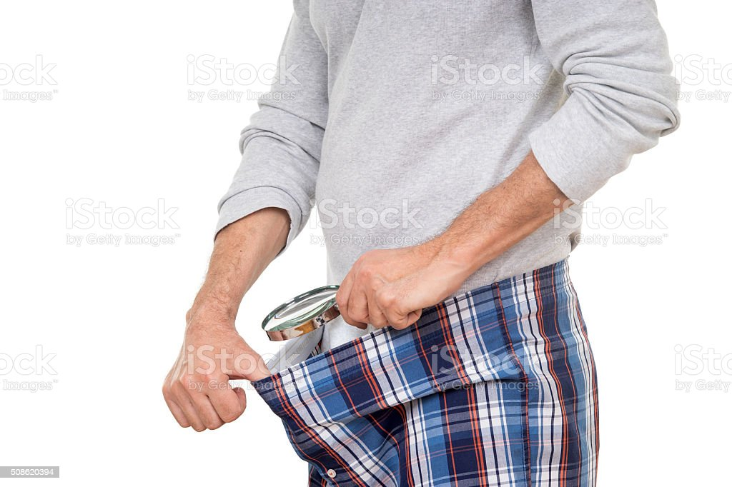 Man with magnifying glass looking into his boxer short stock photo