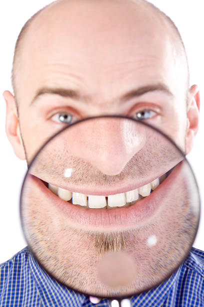 Man with magnifying glass Man with magnifying glass held up to face, enlarging mouth and chin aggrandize stock pictures, royalty-free photos & images