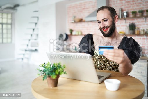 istock Man with make-up using laptop and credit card 1002622128