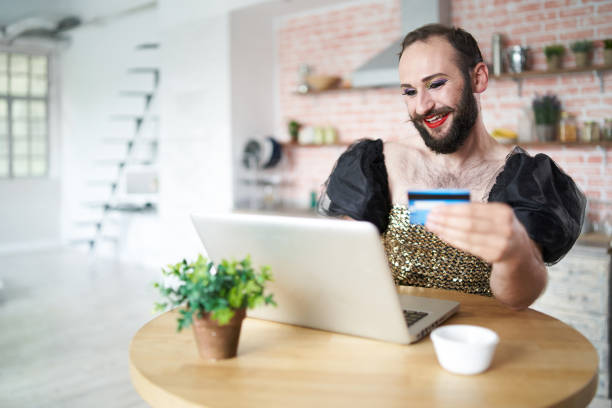 man with make-up using laptop and credit card - apply online stock photos and pictures