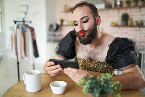 Man with make-up using smart phone