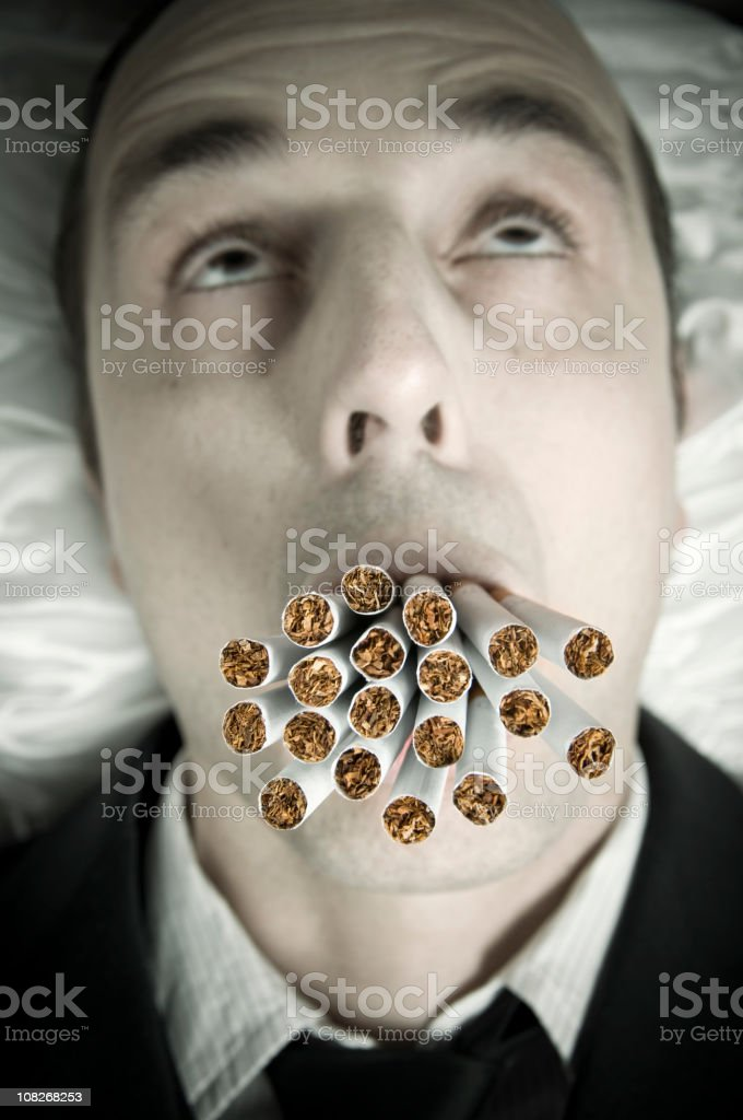 Man with Many Cigarettes in Mouth stock photo