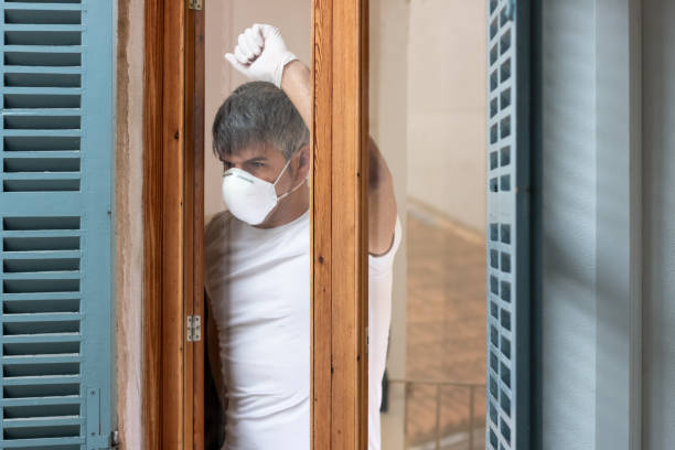 A man with mask and gloves confined at home looking out the window towards the street stock photo