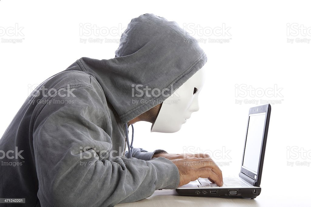 Man With Mask And Hood Using Computer, Internet Security Concept stock photo