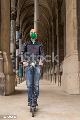mature adult man with green mouth nose mask on electric push scooter in european historical buildings city center in times of coronavirus covid-19