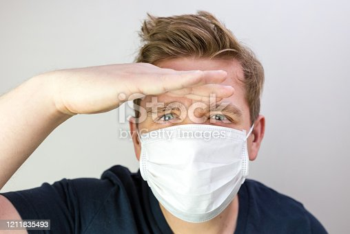 istock Man with mask to protect him from virus. The concept of the epidemic of the coronavirus. Tired Doctor with medical white mask. I don't see, where are you. Man looking far away 1211835493