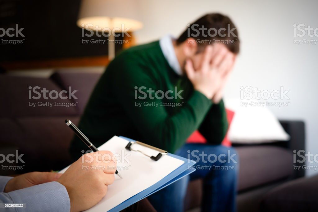 Man with mental health problem in the psychiatrist studio stock photo
