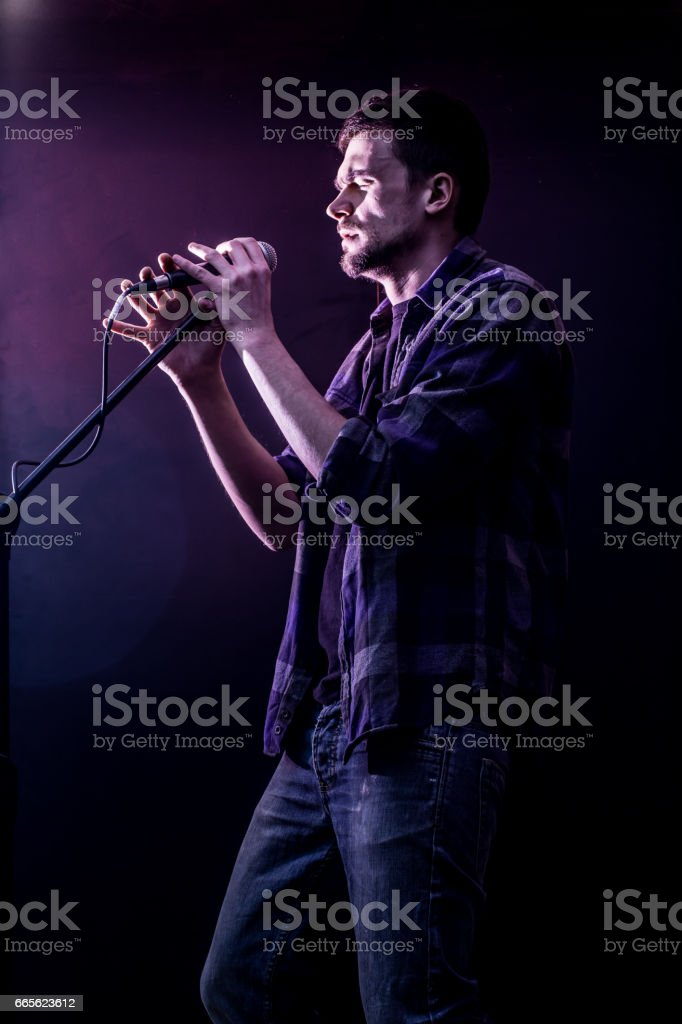 man with microphone on a black background, the music concept,...