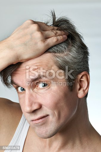 istock Man with mirror looking at his hair 536313479