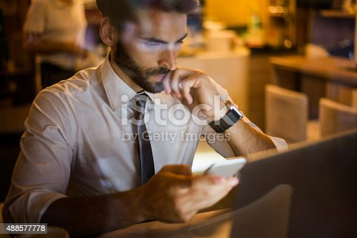 istock Man with mobile phone in coffee shop 488577778