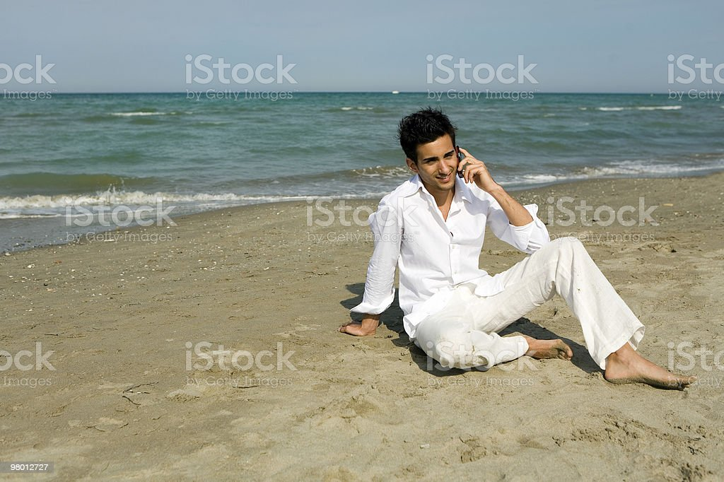 Man with mobile phone sitting at the beach royalty-free stock photo