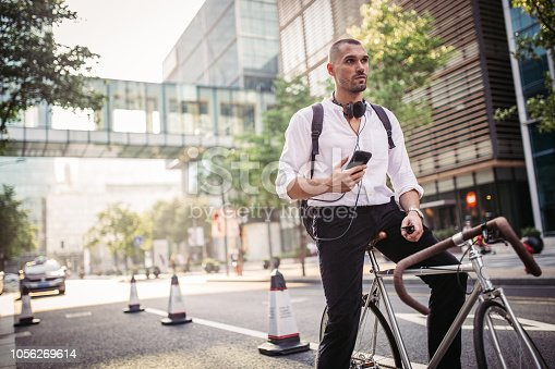 Man with headphones sitting on bicycle outdoors