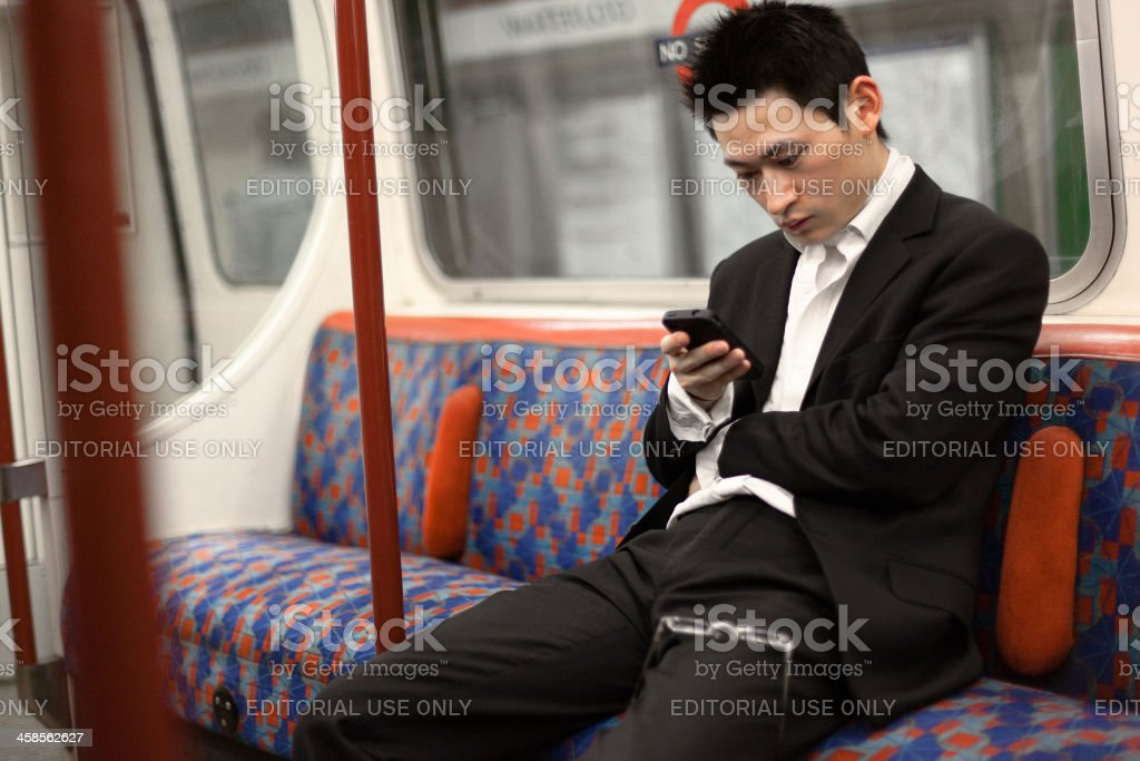 Man with mobile phone traveling in the Tube London royalty-free stock photo