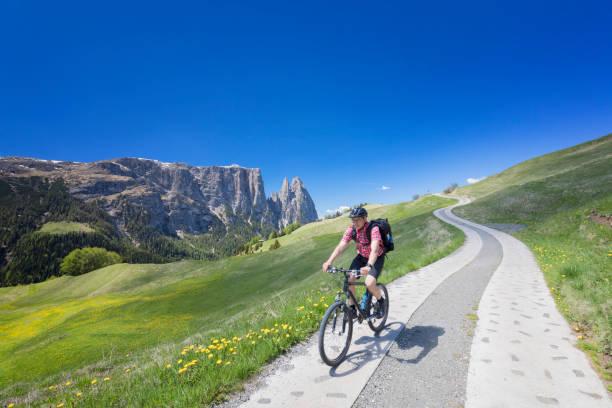 mann mit mountainbike in alpe di siusi - mount schlern im hintergrund - seiser alm stock-fotos und bilder