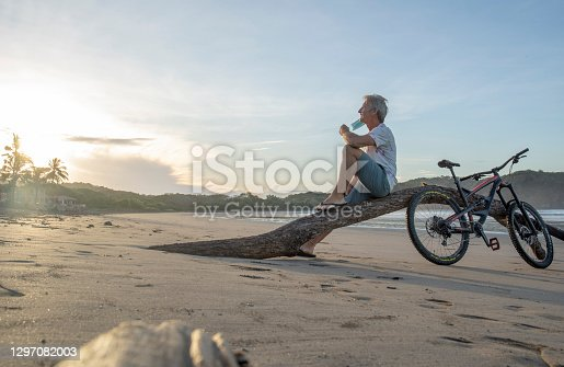 istock Man with mountain bike relaxes on sandy beach at sunrise 1297082003