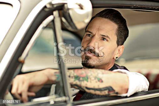istock Man with moustaches sitting  in car 515631761