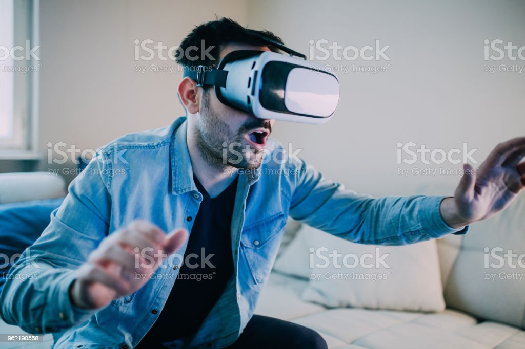 Man with mouth open wearing virtual reality glasses stock photo
