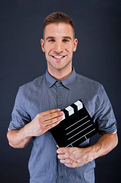 Man with movie clap over dark background stock photo