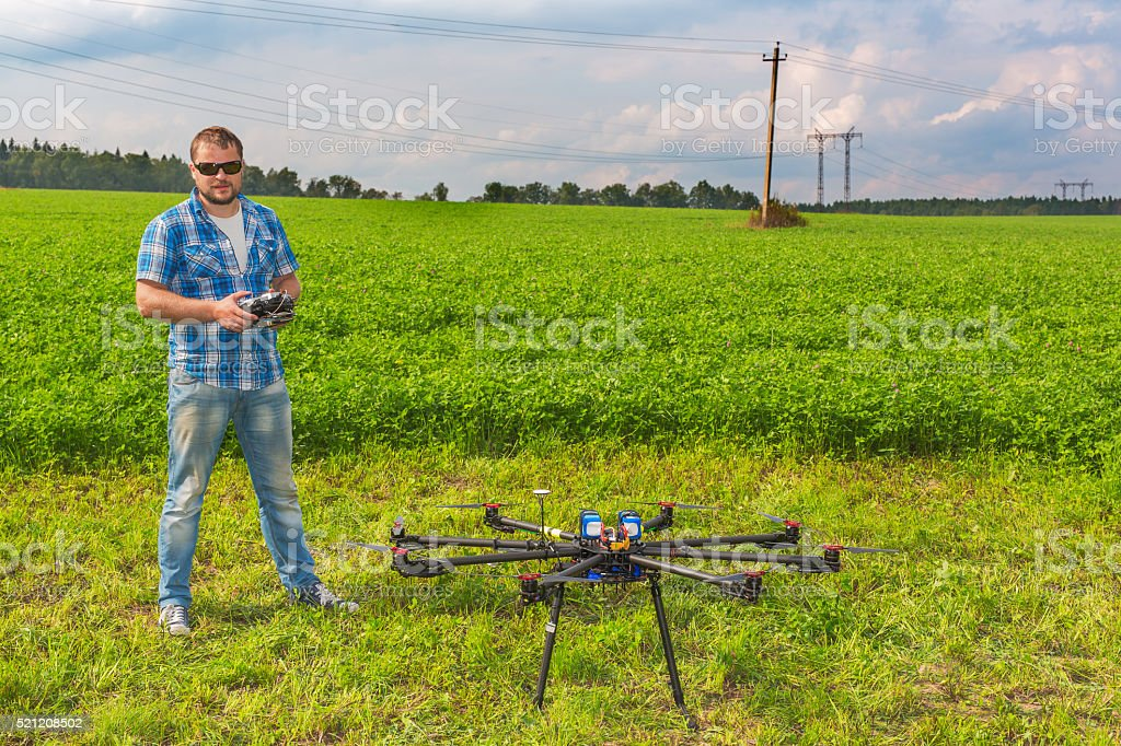 Man with multicopter on ground stock photo