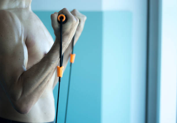 Man with muscular fit torsoand attractive body in 40's exercising with resistance exercise bands in sports club gym. stock photo