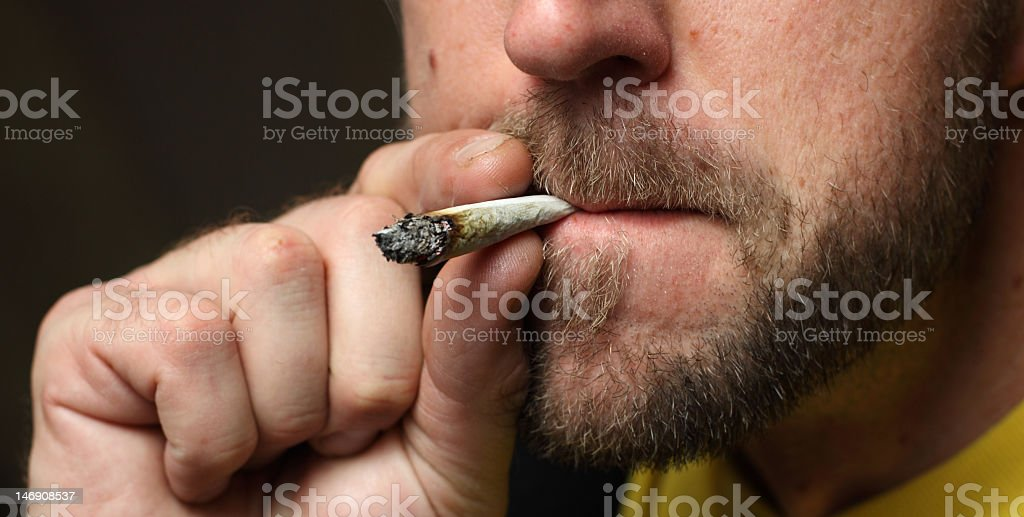 Man with mustache and beard smoking marijuana royalty-free stock photo