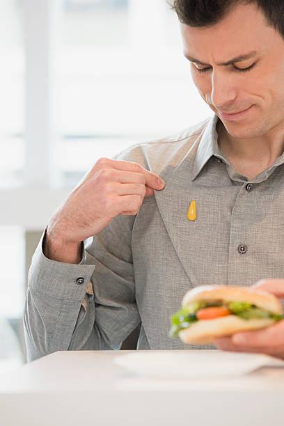 Homem com mostarda na camisa - foto de acervo