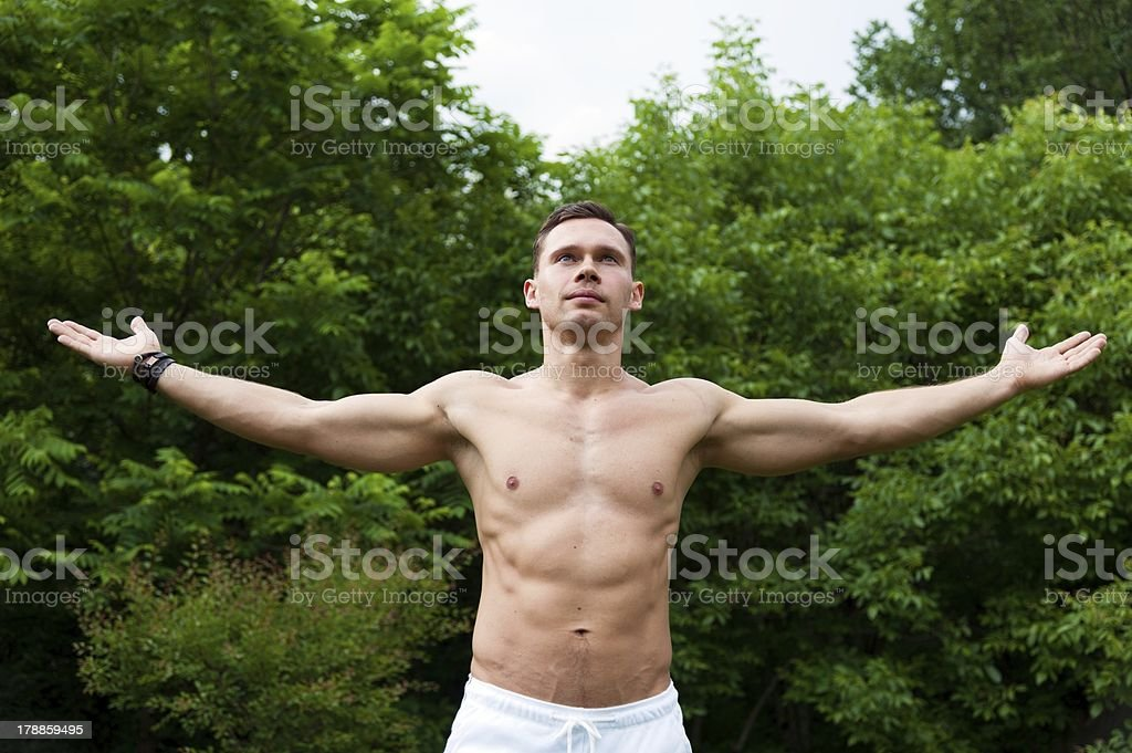 Man with naked torso stands and his hands up stock photo