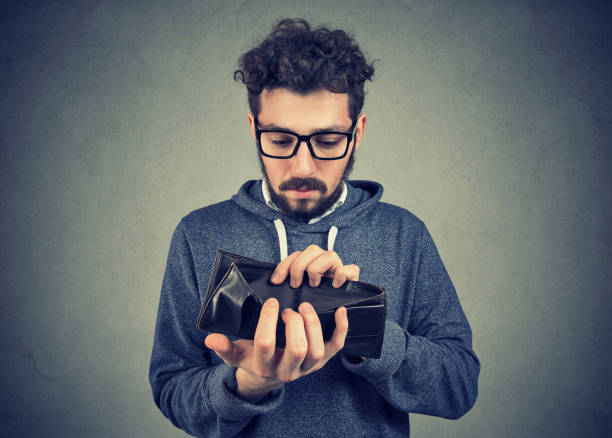 man with no money holding an empty wallet Sad man with no money holding an empty wallet empty wallet stock pictures, royalty-free photos & images