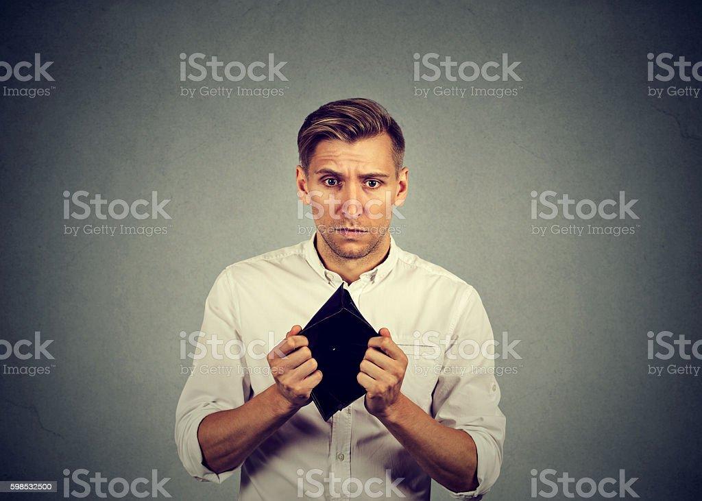 Man with no money holding empty wallet photo libre de droits