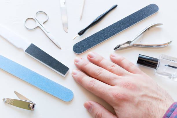 man with not well-groomed nails and tools for manicure man with not well-groomed nails and tools for manicure pedicure manicure men beauty spa stock pictures, royalty-free photos & images