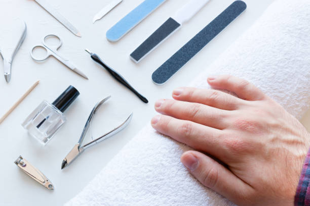 man with not well-groomed nails in the salon of manicure man with not well-groomed nails in the salon of manicure pedicure manicure men beauty spa stock pictures, royalty-free photos & images