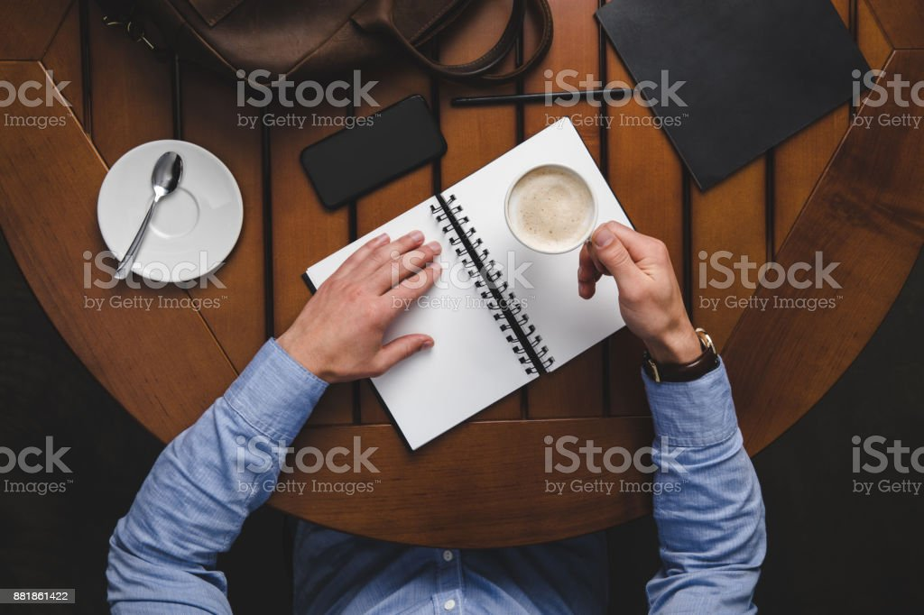 man with notepad drinking coffee stock photo