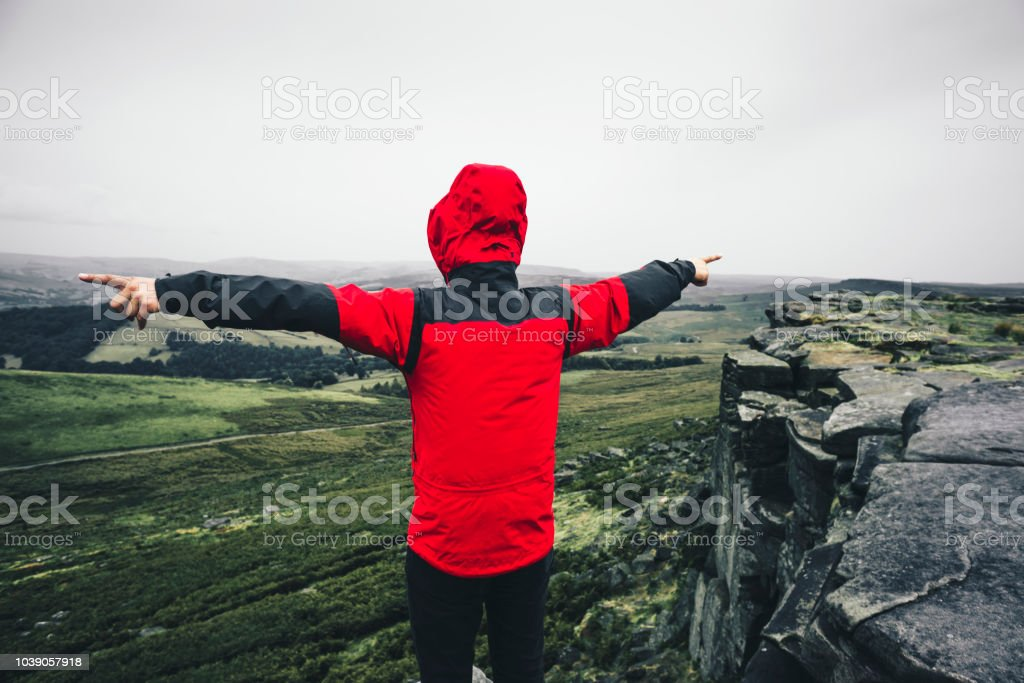 Man in red jacket with arms outstretched standing on the rock