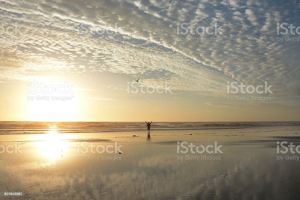 Man with outstretched arms relaxing on the beach. stock photo